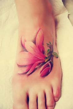 The realistic magnolia tattoo looks like a piece of flower falls on the foot.