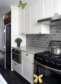 light gray subway tile backsplash with dark grey tile floors and white cabinets. love this. maybe add some white quartz countertops<br>