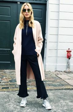Pernille Teisbaek wears a turtleneck sweater, neutral coat, flare jeans, and metallic sneakers
