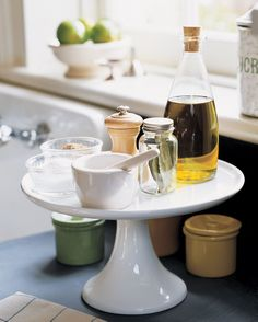 Make the most of your countertops by using a cake stand to hold olive oil, salt, pepper, and other frequently used seasonings. You can arrange even more around the base of the pedestal.