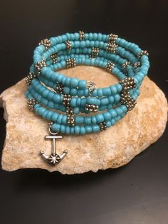 Turquoise seed beads and silver spacer beads hand strung on 5 strands of memory wire topped off with an anchor charm at one end and a turquoise bead charm at the other end. Just wrap on your wrist and go! Memory Wire Jewelry, Handmade Wire Jewelry, Beaded Jewelry Designs, Memory Wire Bracelets, Seed Bead Bracelets, Seed Bead Jewelry, Ankle Bracelets, Healing Bracelets, Bangles