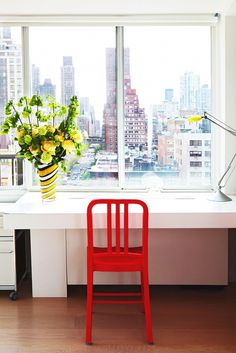 Bright white workspace setup against large window, with a bright red chair and yellow vase with flowers.
