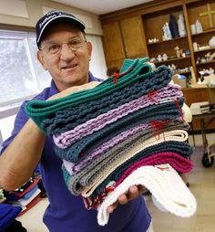 Two dozen residents of 1000 Southern Artery senior housing in Quincy have shipped out 10 boxes filled with nearly 700 scarves and hats to U.S. troops in Afghanistan and other locations. Each item has a tag with a local email address for the residents' Scarves for Troops/Operation Gratitude project. Pictured here: Paul DelGreco with a stack of scarves he helped his friends pack.