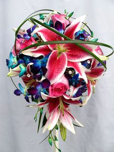 Cascade wedding bouquet with stargazer lilies, blue dendrobium orchids, pink roses with an exotic shadowing of lily grass throughout. floral@kuhlmanns.com