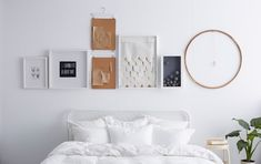 a white wall with frames and objects hanging above it in a straight line