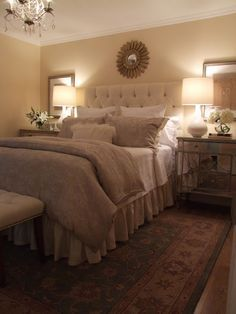 Restful beige bedroom with mirrored night tables and tufted fabric headboard. I'd love to get 2 side mirrors and hang them just like this in your room. We can use one if the 2 round mirrors we already bought above your bed.