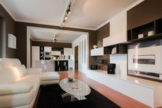 Total #living, composto da #cucina moderna mod. 'Blues' con anta spessore 28 millimetri, laccata bianco lucido e gola finitura bianca.  Il piano di lavoro è in quarzo sp. 2 cm colore bianco.   Elementi a giorno in finitura 'Olmo Dark'.  La zona giorno è stata disegnata con gli stessi colori e materiali della cucina, in modo che l'ambiente cucina e giorno si fonda in un unico spazio.   + #Divano pelle bianca. #sofa #arredamenti #design #interiors