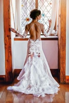 This backless dress with feather adornments looks absolutely stunning! #wedding #weddingdresses #bridal #bridaldresses