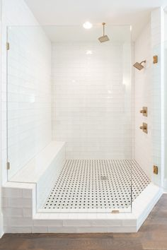 Modern Farmhouse Bathroom Decorating Ideas with a Shower That Features Brick-like White Tile, Black and White Flooring Tile, Gold Fixtures, and an Entire Wall Devoted to Seating