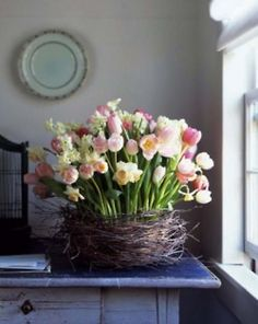 an Easter inspired arrangement including mini daffodils and tulips in a 'nest' of birch twigs