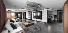 salon ultra moderne avec un mur d'accent en marbre gris et un plafond suspendu avec éclairage indirect led
