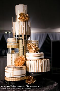 gold and white wedding cake with black accents#GOWS #platinumlist…