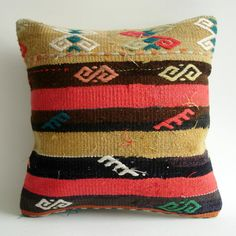 A pillow covered with an antique kilim (a kind of a rug). Its made of wool. Colored with natural dyes. It has Anatolian and Middle Eastern patterns.