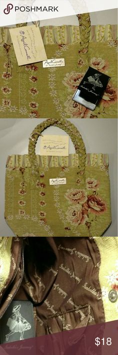 """April Cornell Isabella's Journey Poetry Petite Bag April Cornell for Isabella's Journey Poetry Petite Carpet Bag This is a very pretty olive green with dusty pink tapestry carpet bag. It has a ruffle around the top and braided handles. It has a one snap closure. The interior has a zippered pocket on one side and one pouch pocket on the other side. Comes with a bonus purse mirror, in the photograph. Measures 8"""" tall from just below the ruffle, 12"""" across laying flat and approx 4"""" wide. April…"""
