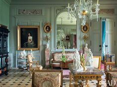 Resting beneath a mirror in the central salon of a French château is a gilt-wood canapé that belonged to the 18th-century hostess Madame Geoffrin; the antique Sèvres statuettes depict literary figures.  PHOTOGRAPHER: Pascal Chevallier HOMEOWNER: Jean-Louis Remilleux