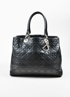 """Classic Christian Dior """"Lady Dior"""" tote in black leather. The perfect bag for everyday use, and great for traveling. Holds all of your essentials plus a small tablet or agenda. Sturdy shape with a fla"""