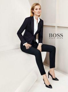 JODIE Dans cette photo, la dame porte un costume noir avec le pantalon noir aussi. Aussi elle porte une chemise blanc. Je pense que la tenue est parfait pour le travaille ou pour quelque chose de professionnel. Aussi dans cette photo, elle porte les chaussures talon hauts noir et c'est toute.