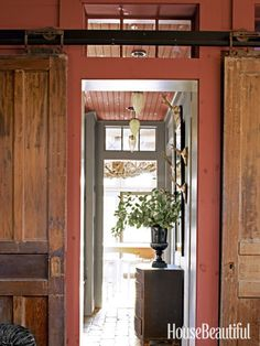 Gorgeous rustic hallway. Love the sliding barn doors via House Beautiful
