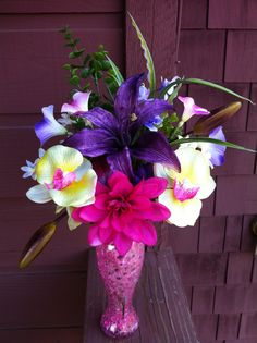 """A colorful Silk Flower arrangement with one large Lily, Orchids surrounded with spring florals and unique greenery. All arranged in a clear glass with pink water beads. Measures approx 13"""" in height x 12"""" in width. $35.00 Created by Jeannie's Floral Creations."""