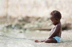 This is an orphan girl from Haiti maybe experiencing the ocean for the first time. Photo by Scott Kelby.
