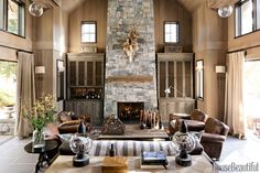 In the living area of a home in Lake Tahoe, California, designer Will Wick updates the traditional mountain retreat with dark stone floors contrasted with whitewashed cedar walls and pale curtains in Altizer & Co. linen. Leather club chairs, Restoration Hardware's Dutch Industrial coffee table, and blackened steel accents add earthy touches to the restrained palette.   - HouseBeautiful.com