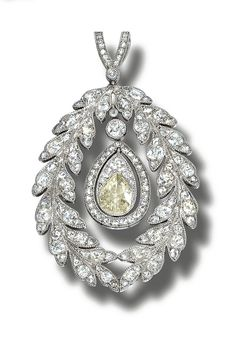 A DIAMOND PENDANT, CIRCA 1910, designed as a wreath of laurel leaves millegrain-set with rose- and circular-cut diamonds, suspending a pear-shaped stone bordered by a line of rose-cut diamonds.