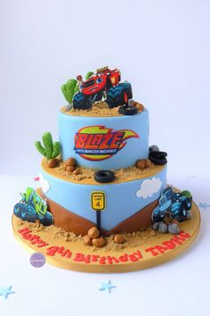 This 2 tier birthday cake is perfect for any Blaze and the monster machines fan. Both tiers have fondant cactus and tyre decorations. Sugar dessert sand and rocks are the setting for Blaze and his friends to get ready to race on. Torta Blaze, Bolo Blaze, Blaze Cakes, Blaze Birthday Cake, 2 Tier Birthday Cakes, Toddler Birthday Cakes, 3rd Birthday, Birthday Ideas, Festa Monster Truck