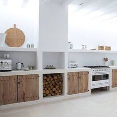 White kitchen with open shelving and logs.
