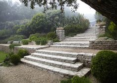 Patrick Dempsey Malibu garden stone staircase ; Gardenista. Recycled concrete walls and pea gravel terraces connect the house to an outdoor kitchen and dining area.