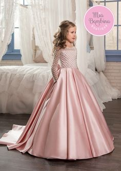 This chic Toronto flower girl dress is a long satin ball gown for vintage-inspired weddings. It features a long-sleeved top embroidered with textured lattice lace all-over. Shining sequins make the top sparkle even brighter. At the back, a beautiful box-pleated skirt boasts a row of covered buttons streaming down towards the short train, while a lovely long bow adds a finishing touch.