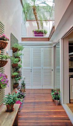 No jardim lateral, acessado por portas de vidro Blindex (os painéis sem moldura da Vidraçaria Mallet medem 1 m de largura e 10 mm de espessura), duas treliças sustentam os vasos de plantas. No andar de cima, vê-se o terraço da suíte.
