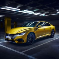The striking kurkuma yellowpaint of the Volkswagen Arteon lets this modern car stand out even more from the dark garage background.