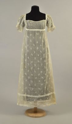 """GRACE FLETCHER WEBSTER SPRIGGED MULL DRESS, 1808 Cotton, empire bodice of embroidered net with short, puffed mull sleeve, net trim; back with drawstring ties and net inserts, slightly trained skirt covered in satin-stitch embroidered sprigs and dotted devices with single side opening, wide tuck above hem. Tag: """"Grace Fletcher Webster"""" (wife of Daniel Webster). Note: Larson acquisition card states Grace Webster gown was acquired from the Daniel Webster family estate. B-26, L 46-49."""