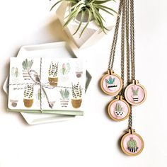 """As featured in Country Living Magazines Holiday Gift Guide 2016 as Best gift for an embroiderer!  Celebrate your love of cacti with a """"plants on pink""""-inspired hand-embroidered hoop necklace. Miniature cacti are hand drawn and stitched onto pink fabric. Each cactus is inside a modern geo print pot.  Miniature hoop pendants are the perfect accessory for the trend-setting, tropical plant and succulent lover. This gift is perfect for you and makes a lovely gift. If you are planning on giving…"""