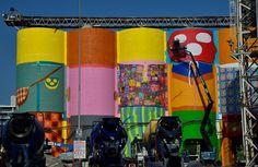 Street Art - ao redor do mundo  A dupla de artistas Os Gêmeos aterrissaram no Canadá, para a Vancouver Biennale, que acontece entre 2014 e 2016.  Um mural 360º, com 20 metros de altura e mais de 2.000 m² foi criado pelos irmãos Gustavo e Otávio Pandolfo em seis gigantescos tonéis, ao lado dos célebres Public Market (Mercado Público), Emily Carr University (Universidade Emily Carr) e False Creek, pequena enseada que separa o centro do restante da cidade.  A região atrai mais de 10,5 milhões…