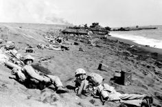 U.S. Marines of the Fourth Division shield themselves in abandoned Japanese trench and bomb craters formed during U.S. invasion and amphibious landing at Iwo Jima, Japanese Volcano Island stronghold, on Feb. 19, 1945 in World War II.  A battered Japanese ship is at right in the background at right.  (AP Photo) #