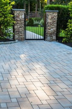 Imagine walking through this beautifully paved entrance everyday. Cambridge Pavingstones with ArmorTec has a wide selection of colors and styles to enhance any walkway.   Contractor: Fine Design Landscapes