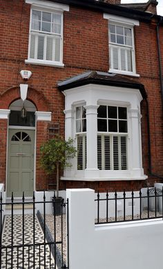 Plastered rendered front garden wall painted white metal wrought iron rail and gate victorian mosaic tile path in black and white scottish pebbles York stone balham london Victorian Front Garden, Victorian Front Doors, Victorian Terrace House, Victorian Homes, Victorian House London, Terrace House Exterior, Victorian Hallway, Green Front Doors, Exterior Front Doors