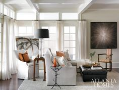 Bathed in natural light and neutral tones, the airy family room is grounded by shades of orange, brown and the couple's colorful art collection. Sheer draperies by Schumacher. Custom sectional from Bungalow Classic in Henry Calvin fabric. Dennis and Leen chair in John Hutton fabric. Console by Hickory Chair.