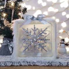 Bring some holiday magic to your home this season with this handmade light up Christmas decoration!  Decorated with white faux fur, warm white Christmas lights, iridescent gems and glittery silver ribbon, this decoration adds a touch of holiday luxury to any room.   Product Details: - 8H x 8L x 3W - 50 count warm Christmas lights inside glass block - Removable bottom to change lights or adjust length of cord -Frosted glass look -Faux fur and ribbon around block -Fake snow glued around edges…