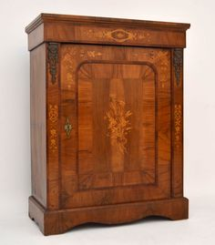 Very impressive figured walnut antique Victorian cabinet with wonderful marquetry & fine inlays all over. It also has the original gilt mounts on top of the sides. This cabinet is in lovely condition having just been French Polished & it has a working lock & key. The top is also inlaid & it has a shaped out plinth. The floral marquetry on the piece is stunning & all original.