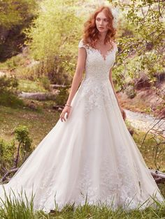 This princess wedding dress features lace appliqués across the bodice, illusion sweetheart neckline, illusion back, and regal hemline. Subtle crosshatch details and sequins add shimmer and dimension…
