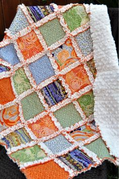 Rag Quilt - (This quilt is retail).  My rag quilt didn't turn out this good.  I like the orange and white between each piece, but the back is solid white.The squares must have been backed with an orange fabric also.
