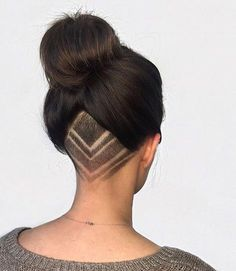 Beautiful undercut with simple shaved design. Long hair worn up in a high bun. Elegant and very lovely.