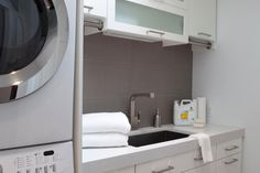 Stacking machines and lots of storage make this small, contemporary laundry room oh so functional