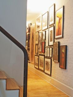 A wooden staircase leads to a white brick gallery wall covered in series of images that have all been matted and framed.