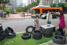group arranges tires to form seating on turf surface in parking space