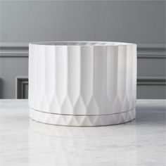 Shop drum white planter.   Bright white stoneware elegantly fluted with movement and texture.  Built-in tray with drainage hole keeps surfaces protected and provides proper drainage.  Perfect for houseplants.