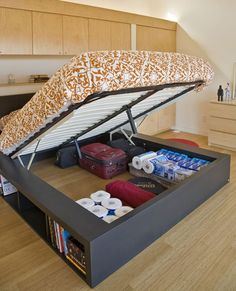 Save Space with Under Bed Storage - This space-saving bed folds up to reveal a hidden storage compartment underneath. Unlike traditional under-bed storage, this secret compartment is tall enough for suitcases and even has bookshelves along the outer edge. Sweet Home, Under Bed Storage, Extra Storage, Hidden Storage, Secret Storage, Food Storage, Underbed Storage Ideas, Shoe Storage For Rv, Easy Storage