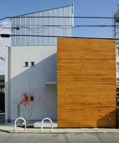 北西角地の西側からの外観。板貼りと左官壁の自然素材で構成し、上層階のみ軽い金属の質感を用いて、3階建てのボリュームを軽減している。